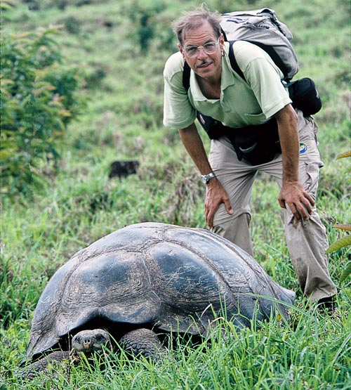 The author, standing next to a dome-shaped tortoise in the highlands of Santa Cruz Island. Photograph by Mark W. Moffett.