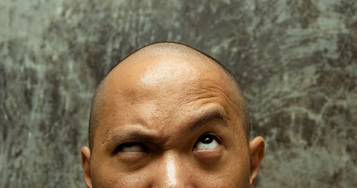man with furrowed brown, looking up