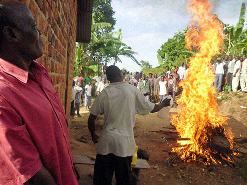 As about 200 people watch, gasoline is poured on a bonfire and the alleged witchcraft items are burned to destroy the evil spirits.