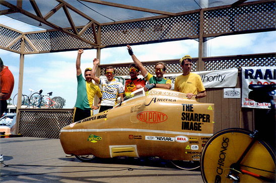 Michael Shermer (second from the right) with his teammates in the 4-man relay team that rode this fully faired recumbent bicycle across America in 1989. Although much faster than a normal upright bicycle on the flats and downhills, recumbents are slower on climbs and do not turn or maneuver as well in turns and traffic.