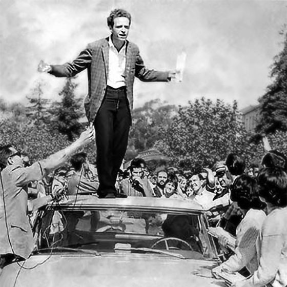 UC Berkeley, Sproul Hall Plaza, October 1 1964. Free Speech Movement advocates, including Mario Savio, speaks from the roof of a police car. They remove their shoes before climbing on the car, in order to do no damage. In the back seat of the car sits an FSM leader whom the police have arrested.