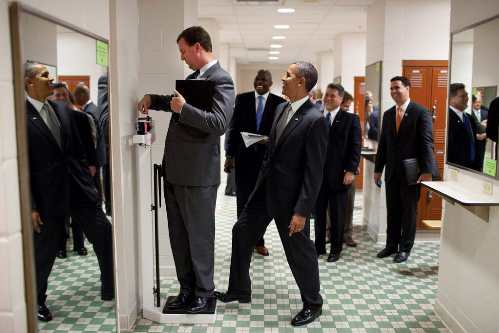 A photograph used as an example of understanding beyond the comprehension of an AI program: President Obama surreptitiously adds a few pounds as a colleague weighs himself. (Credit: Official White House photo by Pete Souza)
