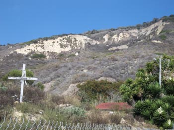 The landslide debris covering the town as of 2011, with the makeshift graves and memorials still standing from 2005. (Courtesy 2011 K. Allison Lenkeit Meezan • Foothill College, Department of Geography • About the Virtual Field Trip  This work is licensed under a Creative Commons Attribution-NonCommercial-ShareAlike 3.0 Unported License.)
