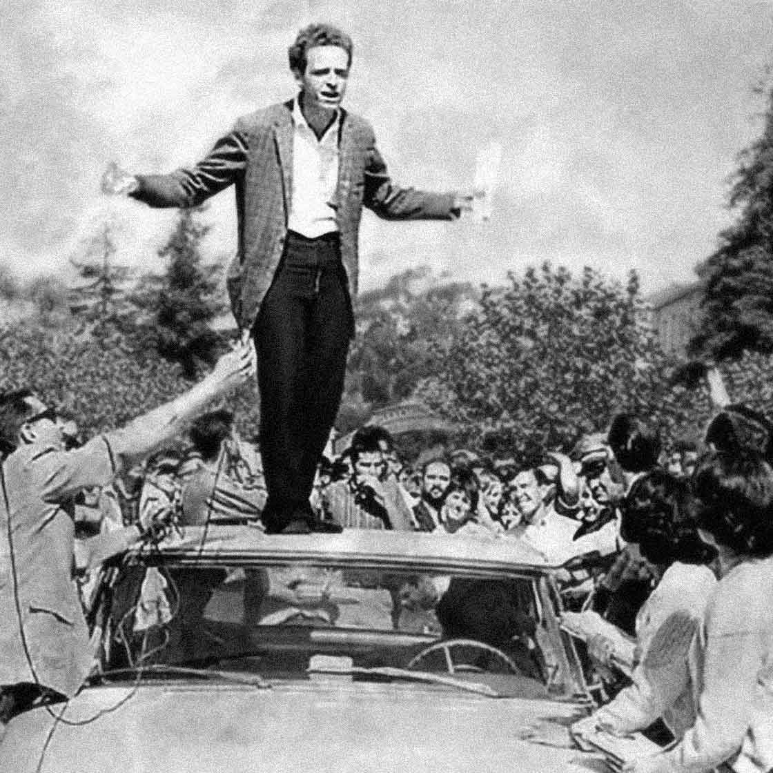 UC Berkeley, Sproul Hall Plaza, October 1 1964. Free Speech Movement advocates, including Mario Savio in this instance, speak from the roof of a police car.